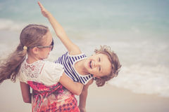 Sister and brother playing on the beach at the day time. Royalty Free Stock Image