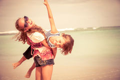 Sister and brother playing on the beach at the day time. Stock Photo