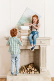 Sister and brother playing with books near fireplace Royalty Free Stock Photography