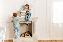 Sister and brother playing with books near fireplace Stock Photography