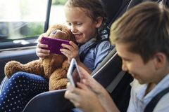 Sister and brother playing with digital devices in the car stock image