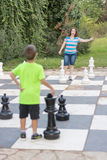 Sister and brother playing giant outdoor chess Stock Images