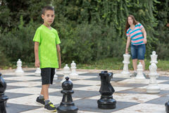 Sister and brother playing giant outdoor chess Royalty Free Stock Photos
