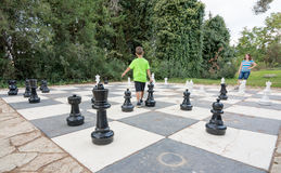 Sister and brother playing giant outdoor chess Royalty Free Stock Photography