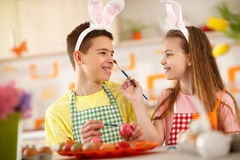 Sister and brother playing while painting Easter eggs Royalty Free Stock Image