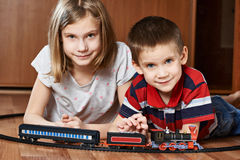 Sister and brother playing with railway Royalty Free Stock Images
