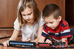 Sister and brother playing with railway Royalty Free Stock Image