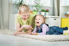 Sister and brother playing in a room Stock Image