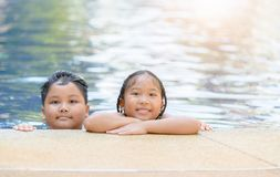 Sister and brother playing at swimming pool stock photos