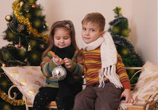 Sister and brother playing under golden Christmas tree Stock Photos