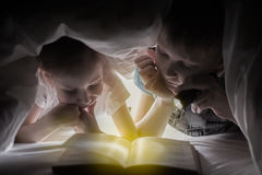 Sister and brother are reading a book under a blanket with flashlight. Pretty young boy and lovely girl having fun in children roo Royalty Free Stock Photography