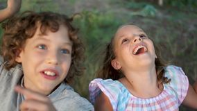 Sister and brother ride in the garden on a swing. Children fool around and build faces. Happy childhood, summer vacation stock video footage