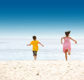Sister and brother running on sandy beach Stock Images