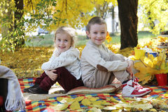 Sister and brother sitting back to back under autumn tree. Smiling sister and brother sitting back to back under autumn tree Stock Photo