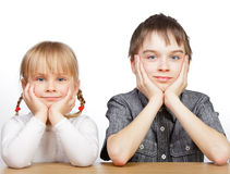 Sister and brother sitting at desk Royalty Free Stock Photo