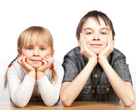 Sister and brother sitting at desk Stock Photos