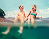 Sister and brother sitting on inflatable mattress and enjoying the sea water, cheerfully laughing when swim in the sea. Careless. Childhood time unusually water stock image