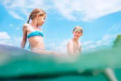 Sister and brother sitting on  inflatable mattress and enjoying the sea water, have fun when swim in the sea. Careless childhood. Vacation time image stock image