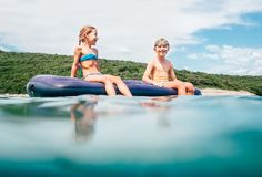 Sister and brother sitting on  inflatable mattress and enjoying the sea water, have fun when swim in the sea with Croatian green. Coast on the background royalty free stock image