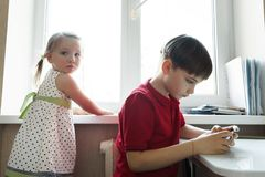 Sister and brother are sitting in the kitchen and playing with the phone royalty free stock image