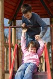 Sister And Brother On Slide Stock Photo