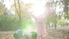 Sister and brother throw yellow leaves into air on background of trees, playing in backlight. Sister and brother throw yellow leaves into the air on background stock video footage