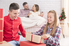 Sister and brother unwrapping gifts. Sister and brother unwrapping christmas gifts, happy parents in background Stock Photography