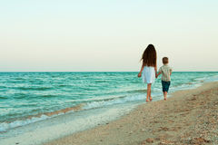 Sister and brother walking away by the evening beach. Stock Image
