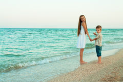 Sister and brother walking away by the evening beach. Royalty Free Stock Images