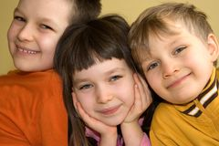 Sister And Brothers. Horizontal portrait of a young girl between her two brothers.  All are smiling.  The little girl has her hands cupping each side of her face Royalty Free Stock Images