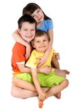 Sister and brothers. A sister and two brothers are hugging while they are sitting. Isolated on a white background stock image