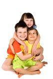 Sister and brothers. A group of three young children. There is a sister and two brothers all hugging while sitting on the floor. Isolated on white background royalty free stock image