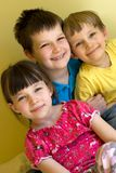 Sister and brothers. A sister and two brothers are hugging while they are sitting. They are against a yellow background stock image
