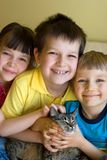 Sister, brothers and cat. A sister and two brothers are smiling as they are hugging their pet cat royalty free stock photos