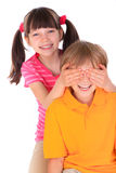 Sister covering brother's eyes Stock Photography