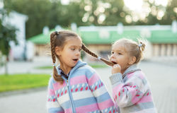 Sister dabbles and bites her braid older Royalty Free Stock Photos