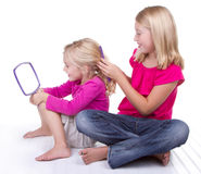Sister doing younger sisters hair Stock Photo