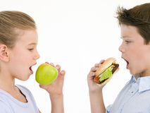 Sister eating apple by brother eating cheeseburger Stock Photos