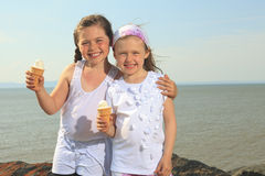 Sister eating ici-cream in front of ocean Royalty Free Stock Photography