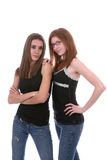 Sister Fashion. Thin young women in black and denim jeans looking tough but beautiful Stock Photography