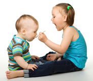 Sister is feeding her little brother Stock Photos