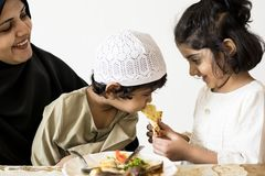 Sister feeing brother in a family dinner stock images
