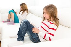 Sister friends kid girls playing with tablet pc in sofa Stock Photography