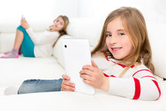 Sister friends kid girls playing with tablet pc in sofa Stock Images