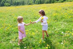 Sister girls in meadow playing with spring flowers Royalty Free Stock Photos