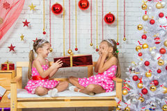 Sister gives girl a gift, girl peeking through closed eyes palms Stock Photos