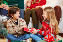 Sister giving brother gift at Royalty Free Stock Images