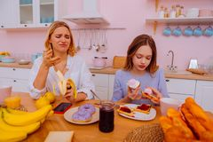 Sister having healthy diet feeling disguise looking at sweets. Feeling disguise. Blonde-haired sister having healthy diet feeling disguise looking at sweets royalty free stock photography