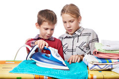 Sister helps younger brother to properly handle iron isolated Royalty Free Stock Images
