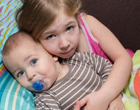Sister and her brother snuggled up on a bed at home. Stock Photography